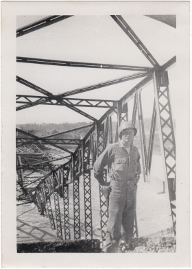 <h5>Downed Bridge</h5><p>Appears to be Clint Stillman in front of a destroyed bridge. Provided by the family of Ivo Schommer.</p>