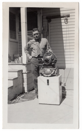 <h5>Clinton Stillman</h5><p>Clinton Stillman posing in front of old diving suit.  Photo provided by family of Ivo Schommer.</p>